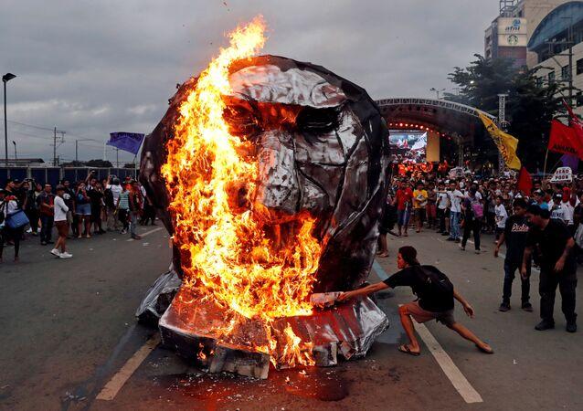 ناشطون يحرقون تمثالًا للرئيس الفلبيني رودريغو دوتيرتي لدى إلقائه خطابا حول حالة الأمة في مجلس النواب في مدينة كيزون-سيتي، مانيلا، الفلبين 23 يوليو/ تموز 2018