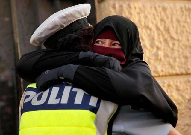 آية، 37 عاما، منقبة، تحتضن ضابط شرطة خلال مظاهرة ضد حظر الحجاب في كوبنهاغن، الدنمارك 1 أغسطس/ آب 2018