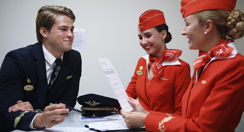 مضيفات الطيران لشركة طيران آيروفلوت الروسية، أناستاسيا بيلوسوفا ونيكيتا دوكا، وكبير المضيفين في شركة طيران آيروفلوت ماريا تروفيموفا في مبنى مطار شيريميتيفو بموسكو