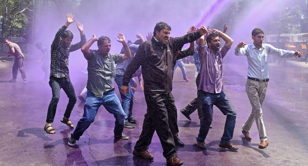 معلمون كشميريون يحتجون بشعارات مناهضة للحكومة بينما تفصلهم الشرطة الهندية بالمياه الملونة الأرجوانية خلال احتجاج في سريناجار في 9 أغسطس/ آب 2018