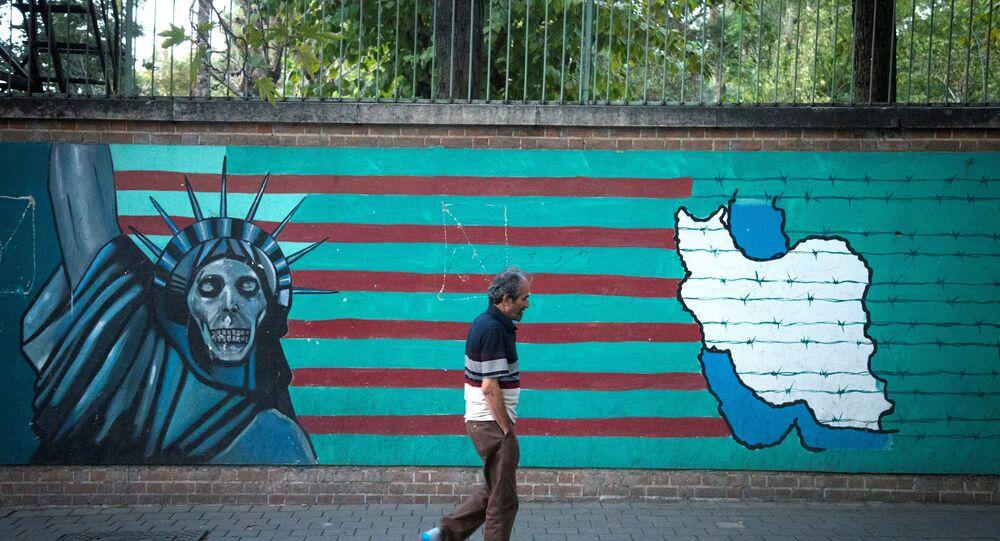 رجل يسير على خلفية جدارية في أحد شوارع طهران، إيران