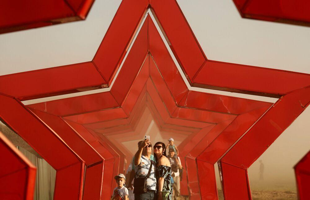 زوار يلتقطون صور سيلفي على خلفية شعار لمسابقة الألعاب العسكرية الدولية أرمي -2018  (الجيش - 2018) في حقل بيسوتشنوي في حقل ألابينو بضواحي موسكو