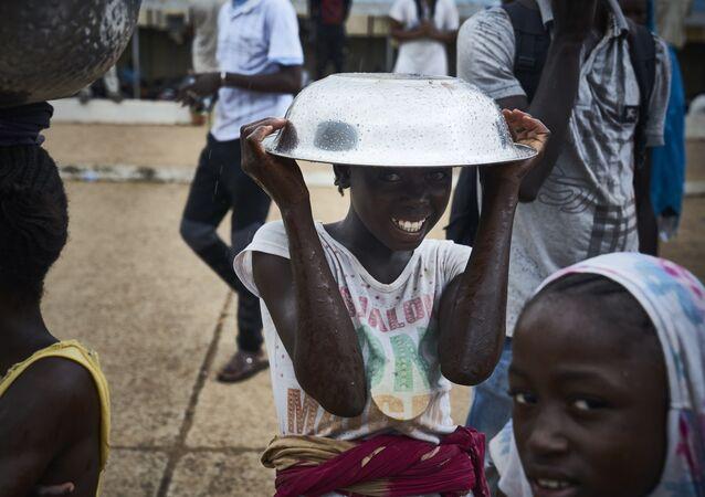 فتاة تقف مع وعاء معدني فوق رأسها على هامش احتجاجات ضد الرئيس المالي الحالي في باماكو في 11 أغسطس/ آب2018 ، عشية الجولة الثانية من الانتخابات الرئاسية في مالي.