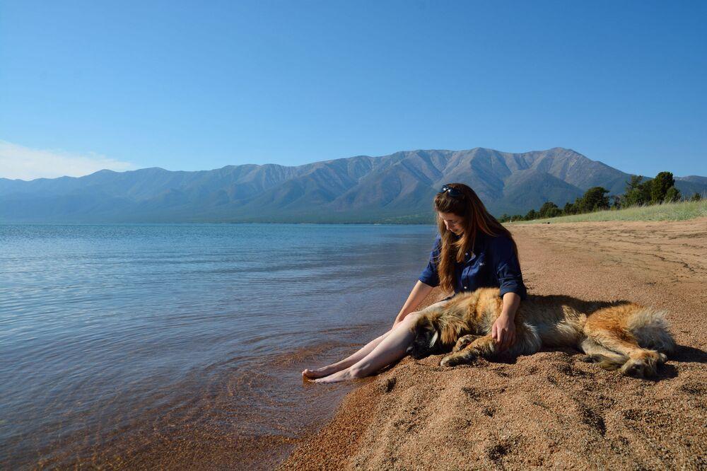 فتاة وكلبها يستجمان على شاطئ بحيرة بايكال