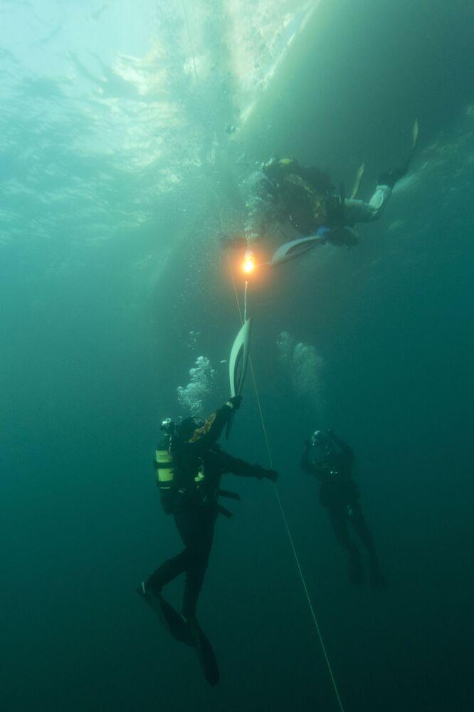 مقدمة برامج تلفزيونية يكاترينا أندرييفا (يسار) تحمل الشعلة الأولمبية خلال الغطس في عمق بحيرة بايكال، استعدادا لدورة الألعاب الأولمبية الشتوية في سوتشي 2014