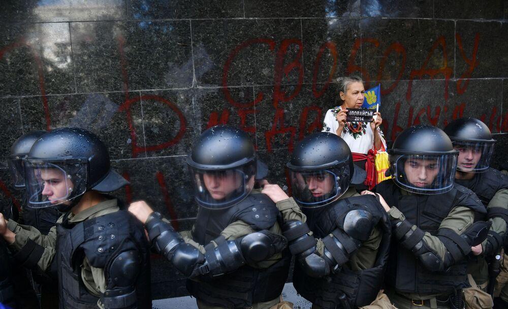 امرأة تقف خلف عناصر شرطة مكافحة الشغب الأوكرانية، أمام مكتب المدعي العام في كييف، لمنع هجمات نشطاء الجماعات اليمينية المتطرفة، أوكرانيا 17 سبتمبر/ أيلول 2018