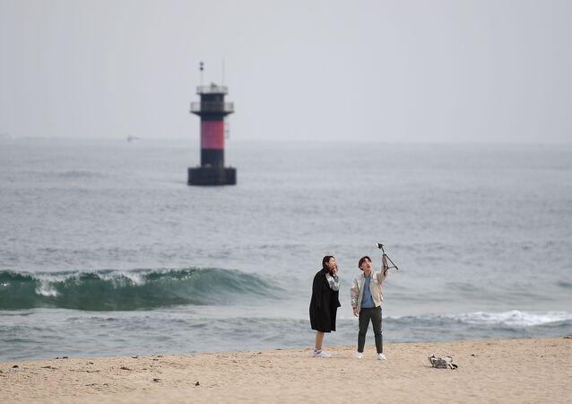 شخصان يلتقطان صورة سيلفي على خلفية شاطئ مدينة غانغننغ، كوريا الجنوبية