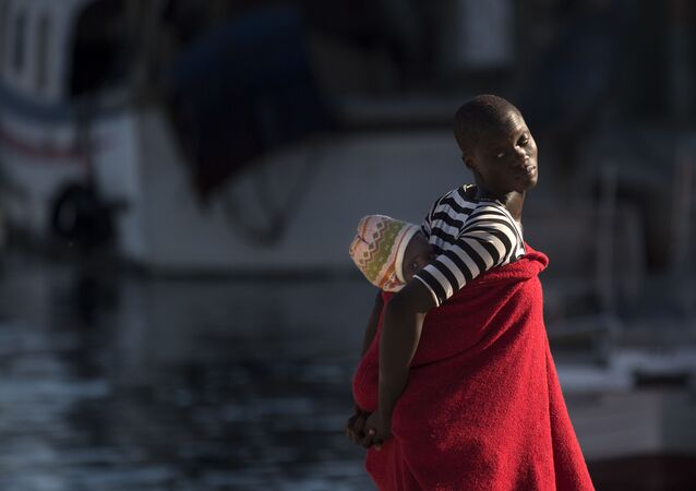 لاجئة تحمل طفلها على ظهرها في ميناء مالقة، إسبانيا 23 سبتمبر/ أيلول 2018