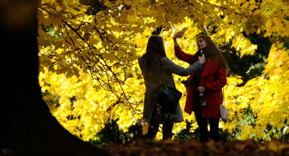 فتاتان تلتقطان صور سيلفي على خلفية أشجار الخريف في منتزه كولومينسكويه الحكومي في موسكو