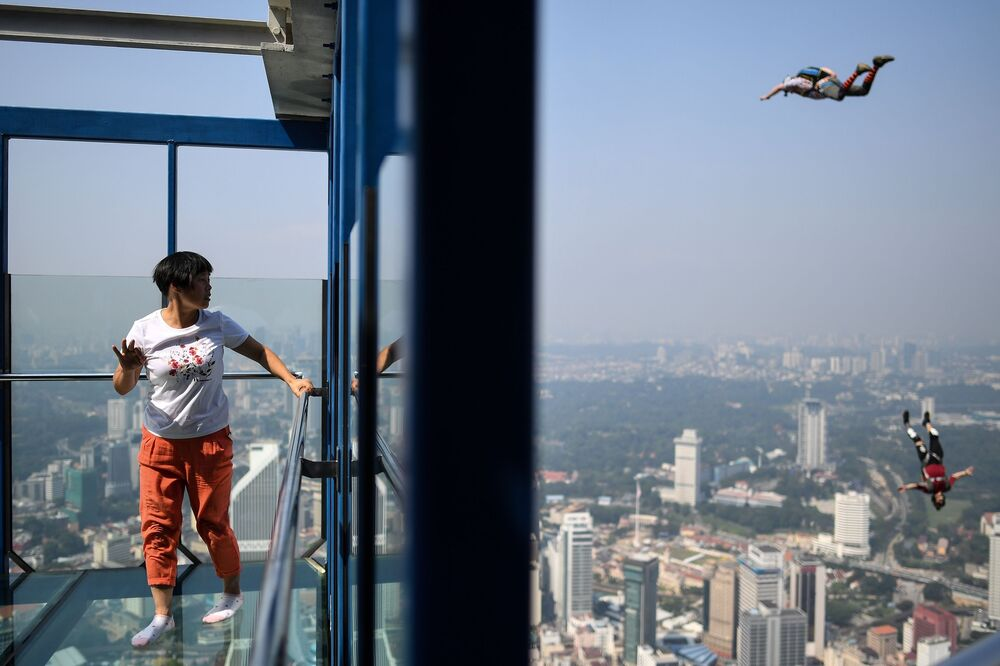 سائحة تنظر إلى القافزين من قاعدة القفز Kuala Lumpur Tower، من على ارتفاع 300 متر، في برج كوالا لمبور، ماليزيا في 30 سبتمبر/ أيلول 2018