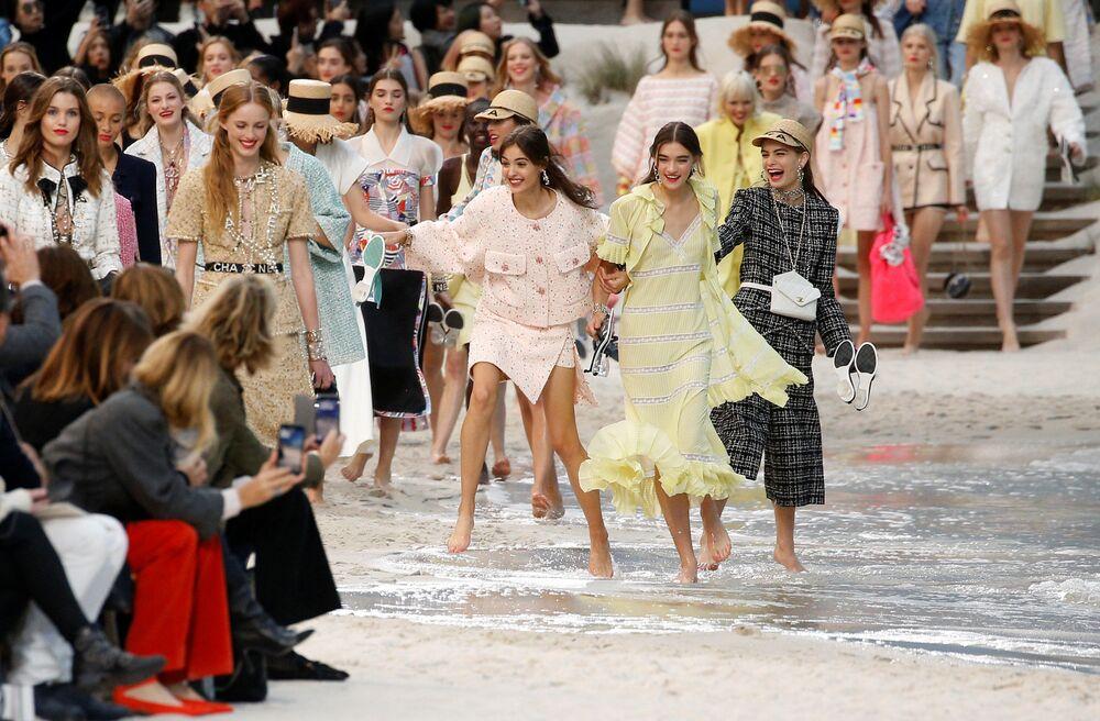 عارضات أزياء يقدمن تصاميم إبداعية من المصمم الألماني كارل لاغرفيلد، كجزء من عرض مجموعة الأزياء الجاهزة للنساء ربيع-صيف 2019، لدار أزياء شانيل على الشاطئ خلال أسبوع الموضة في باريس، 2 أكتوبر/ تشرين الأول 2018