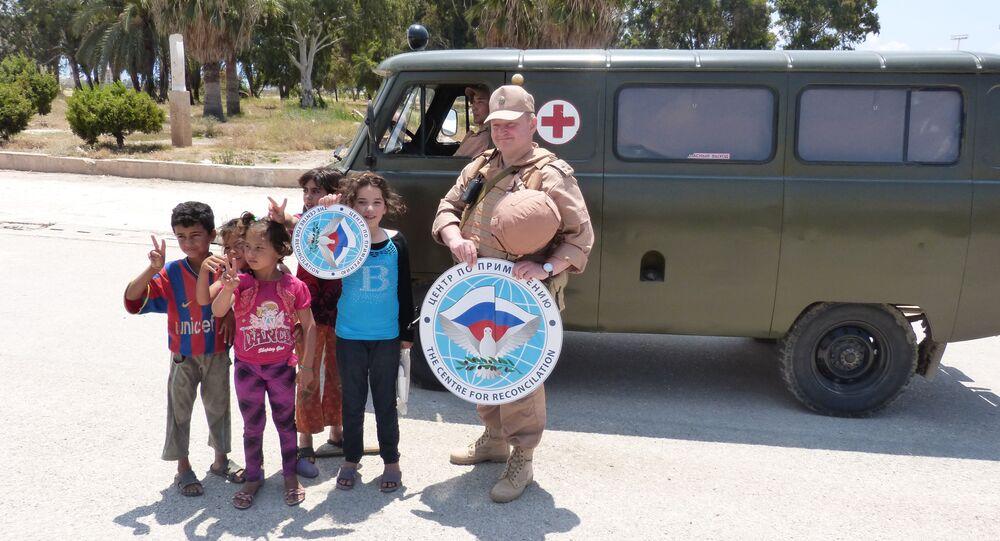 جندي من مركز المصالحة الروسي في سوريا مع اطفال سوريين