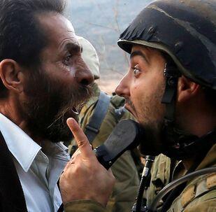 شجار بين رجل فلسطيني وجندي إسرائيلي  خلال الاحتجاجات بإغلاق مدرسة بالقرب من مدينة نابلس، الضفة الغربية، فلسطين، 15 أكتوبر/ تشرين الأول 2018
