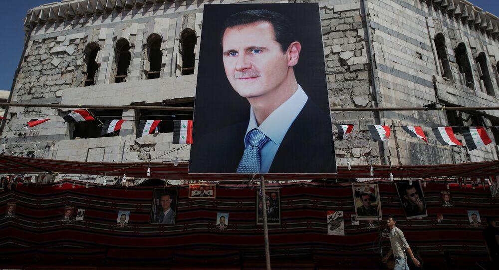 رجل يسير على خلفية لافتة تحمل صورة الرئيس السوري بشار الأسد في دوما، سوريا  17 سبتمبر/ أيلول 2018