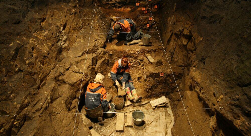 موظفو معهد الآثار والاثنوغرافيا التابع لفرع سيبيريا التابع للأكاديمية الروسية للعلوم خلال العمل الأثري في أحد قاعات كهف دينيسوفا