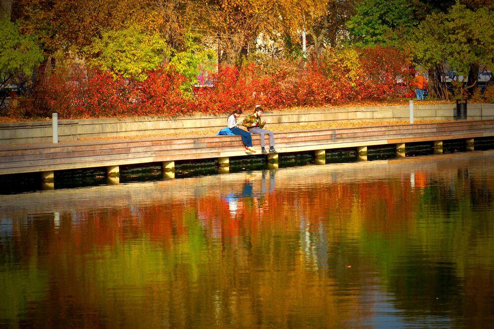 أشخاص يجلسون على ضفة مستنقع مائي في حديقة غوركي بموسكو
