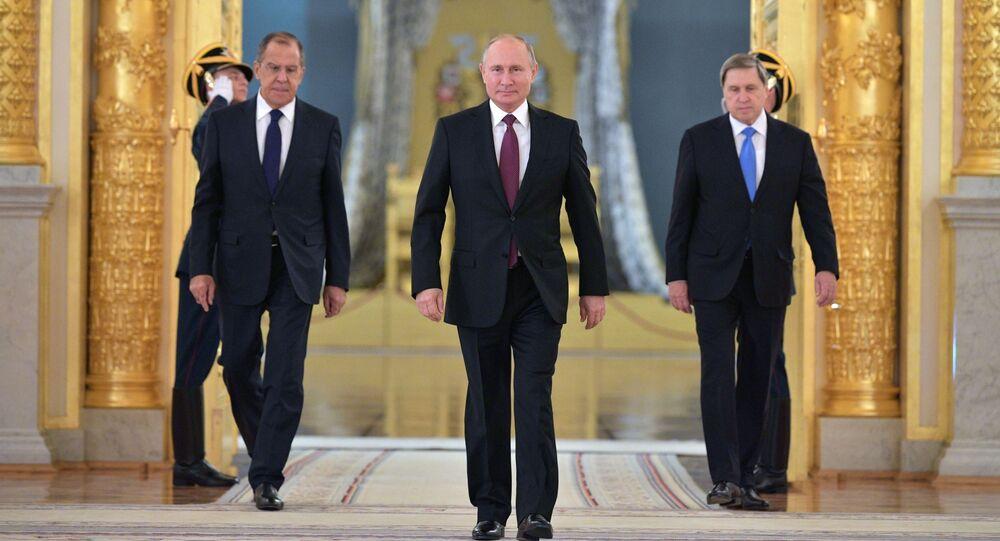 الرئيس فلاديمير بوتين ووزير الخارجية الروسي سيرغي لافروف والمساعد الرئاسي يوري أوشاكوف لدى وصولهم قاعة ألكسندر في الكرملين، لحضور مراسم اعتماد وقبول سفراء الدول الأجانب في موسكو