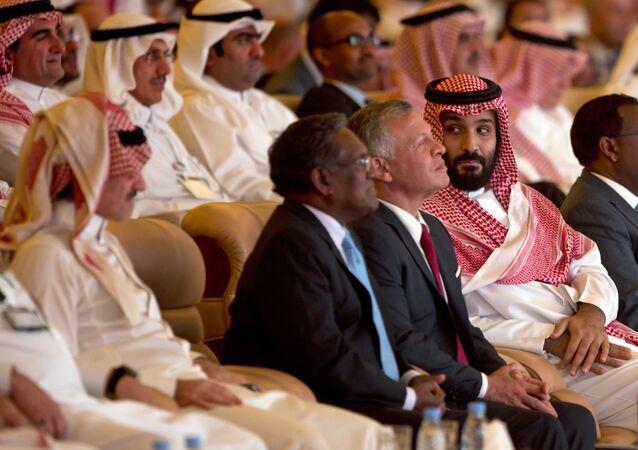 ولي العهد السعودي محمد بن سلمان ينظر إلى الملياردير السعودي الأمير الوليد بن طلال إلى اليسار  بينما يجلس بجانبه العاهل الأردني الملك عبد الله الثاني خلال مؤتمر مبادرة الاستثمار المستقبلية في الرياض