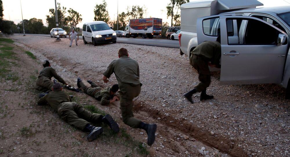 جنود ومدنيون إسرائيليون يحتمون بعد أصوات صفارات الإنذار الجوية على طريق في الجانب الإسرائيلي من الحدود مع غزة