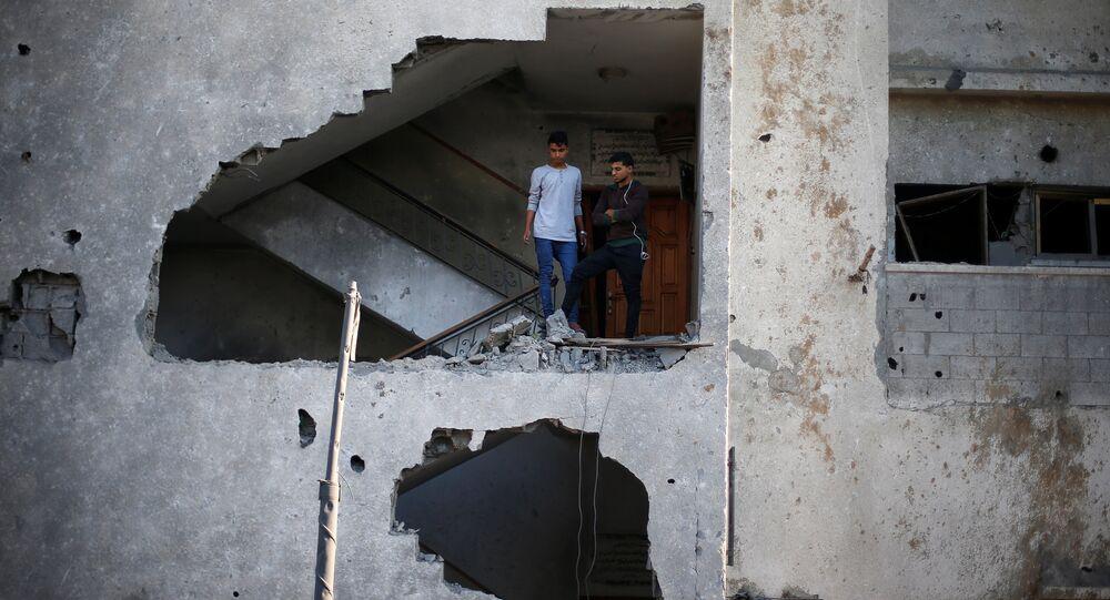 فلسطينيون ينظرون إلى منازلهم التي تهدمت في غارة جوية إسرائيلية على مدينة غزة