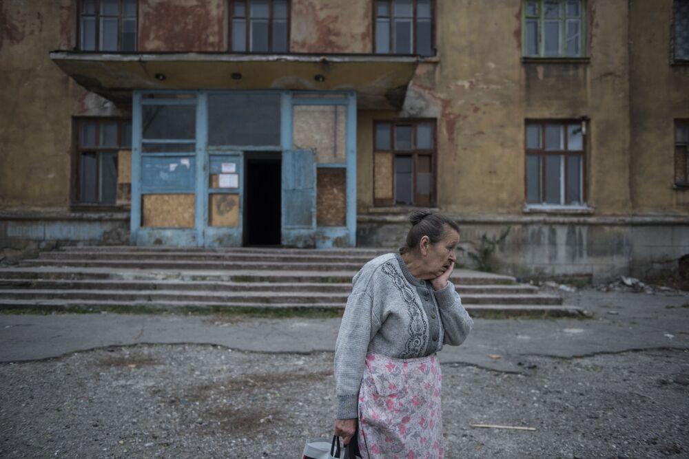 مواطنة تقف أمام مبنى سكني بمدينة ماكييفكا في منطقة دونيتسك، أوكرانيا