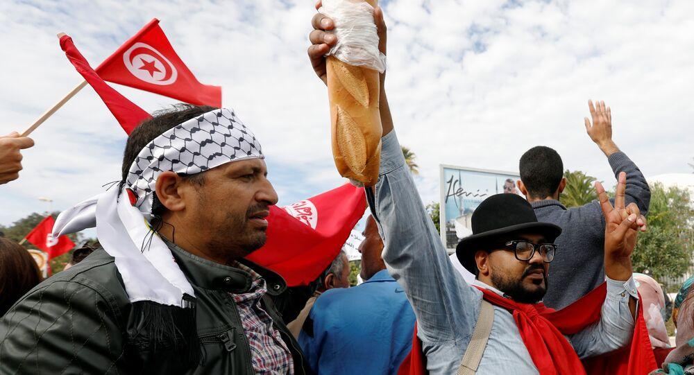 رجل يحمل الخبز أثناء احتجاج ضد رفض الحكومة رفع الأجور في تونس