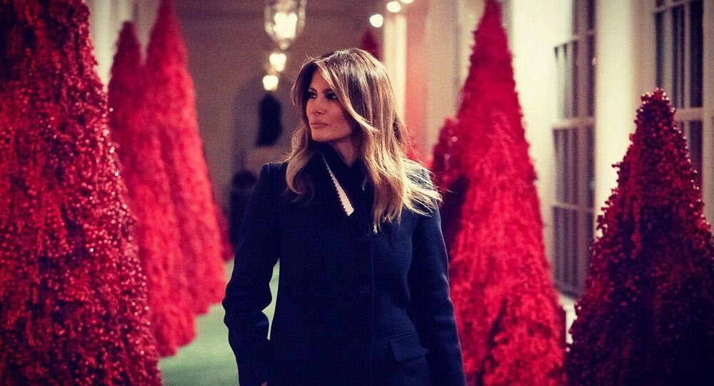 ميلانيا ترامب وخلفها أشجار عيد الميلاد باللون الأحمر في البيت الأبيض