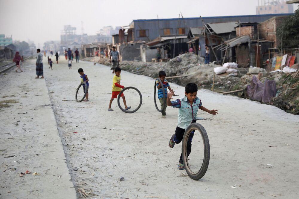 أطفال يلعبون بالعجل في مدينة دكا، بنغلادش