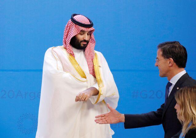 رئيس الوزراء الهولندي مارك روتي يومىء خلال حديثه مع شخص آخر بينما يسير متجاوزا ولي العهد السعودي محمد بن سلمان