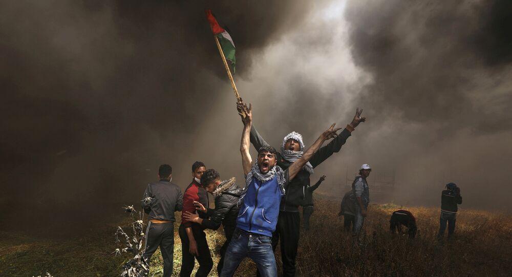 صورة العام لـ2018: متظاهرون فلسطينيون يصرخون خلال مواجهات مع القوات الإسرائيلية في مظاهرة مطالبين بحق العودة إلى وطنهم على الحدود بين إسرائيل وشرق مدينة غزة