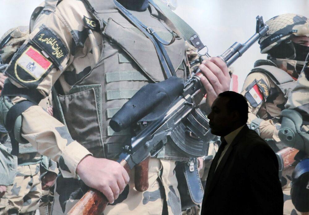 زائر يسير على خلفية منشرو للجيش المصري معرض إيديكس 2018 في القاهرة، 3 ديسمبر/ كانون الأول 2018