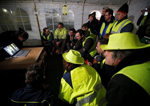 متظاهرون تابعون لحركة السترات الصفراء يشاهدون كلمة الرئيس الفرنسي داخل الخيام