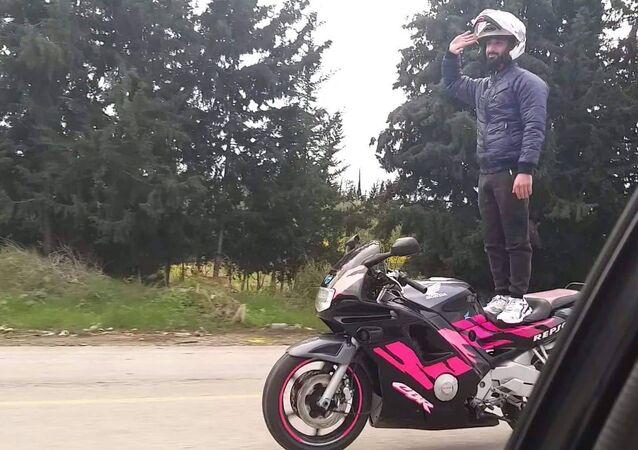 الشاب السوري دكوان حسن وهو يقف على دراجته النارية