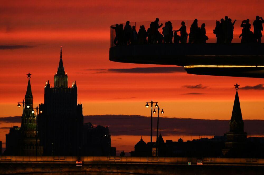 زوار وسياح على الجسر الطائر (بورياشيي موست) في حديقة زارياديه وسط مدينة موسكو، وعلى خلفيته: أبراج الكرملين ومبنى وزارة الخارجية الروسية