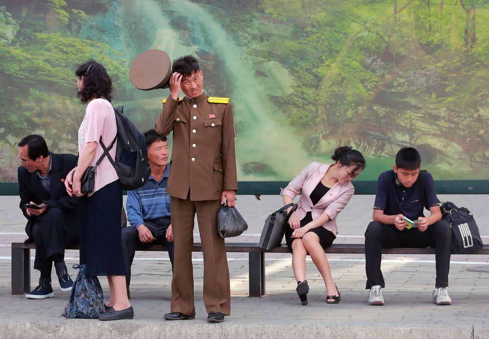 مواطنون بمحطة الباص في مدينة  بيونغ يانغ، كريا الشمالية