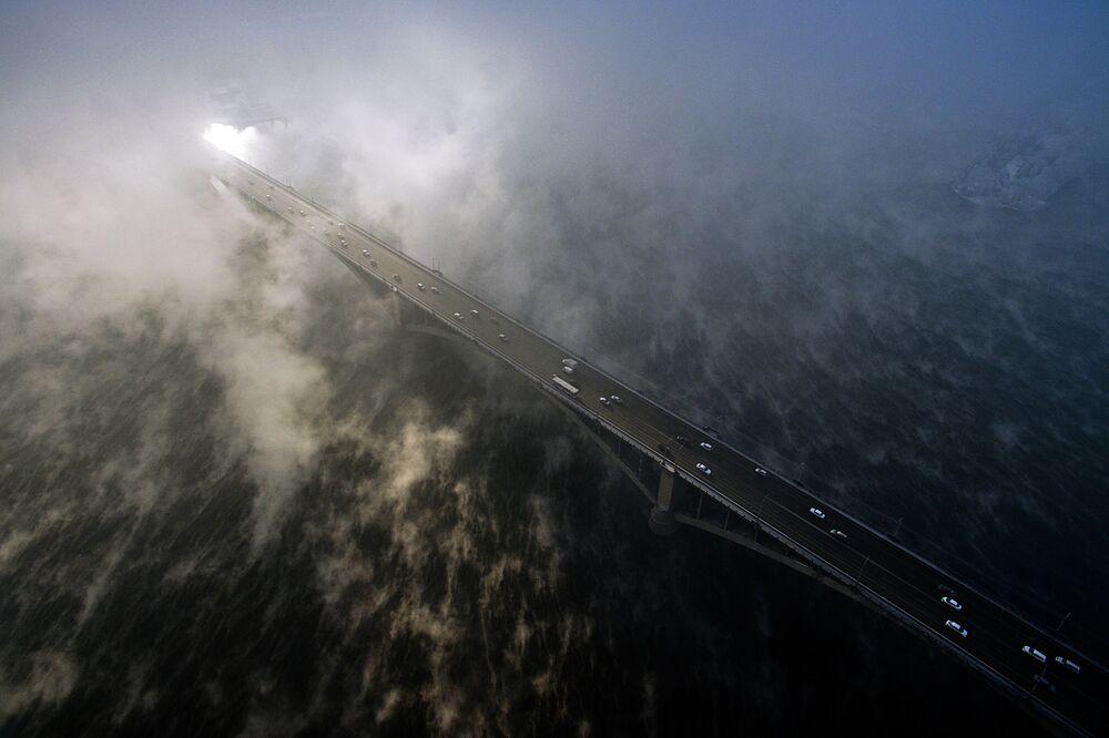 سيارات تسير على جسر كومونالني فوق نهر ينيسي