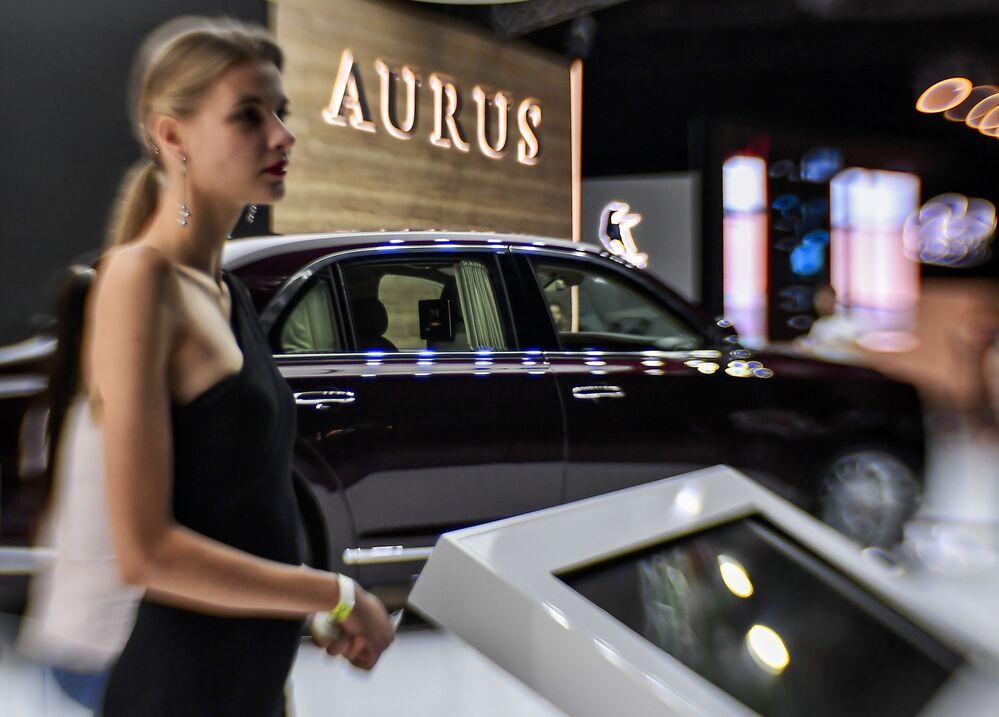 فتاة تقف أمام سيارة Aurus Senat في المعرض الدولي للسيارات لعام 2018