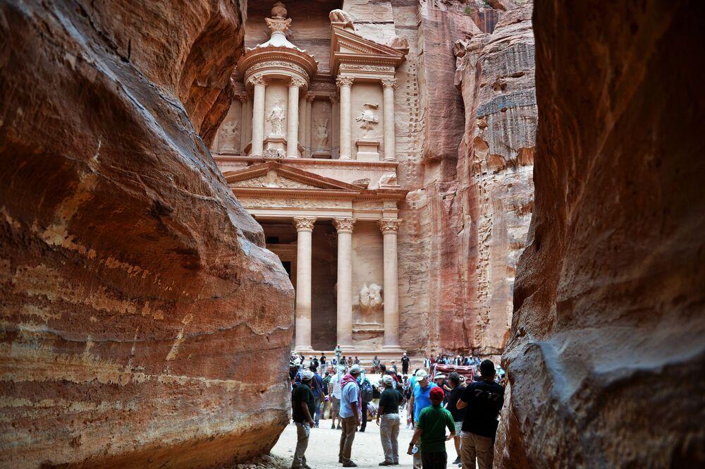 السائحون يزورون مقابر البتراء بالمعبد الصخري في الخازن (خزنة الفرعون) في مدينة البتراء القديمة في الأردن.