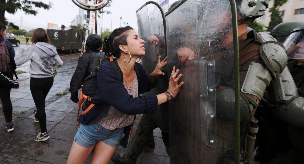 ناشطة من عشيرة مابوتشي تحاول وقف حركة عناصر الشرطة، أثناء مظاهرات في سانتياغو، تشيلي 14 ديسمبر/ كانون الأول 2018