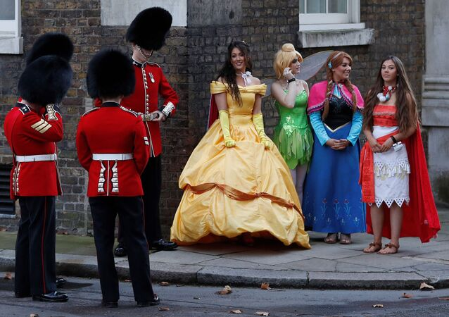 أعضاء الحرس الويلزي يقفون على خلفية فتيات يرتدين أزياء شخصيات من أفلام كرتون ديزني في وسط العاصمة لندن، إنجلترا 17 ديسمبر/ كانون الأول 2018 وذلك في إطار الاحتجاجات ضد بريكسيت.
