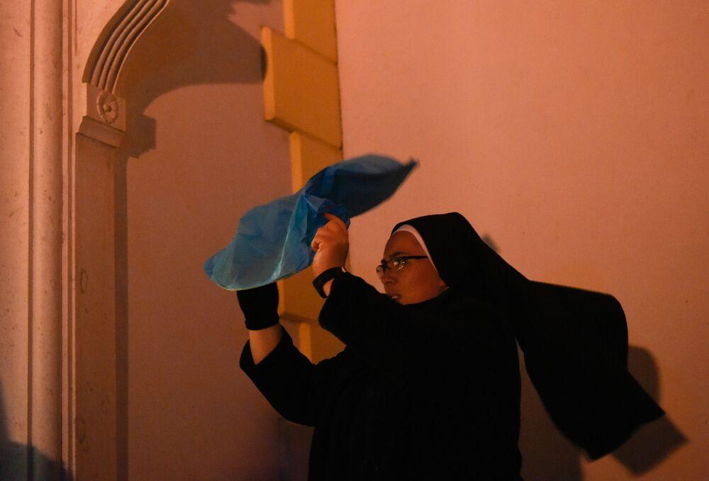 راهبة تحاول إشعال فانوس بعد احتفالات قداس عيد الميلاد في كنيسة غرب كوسوفو
