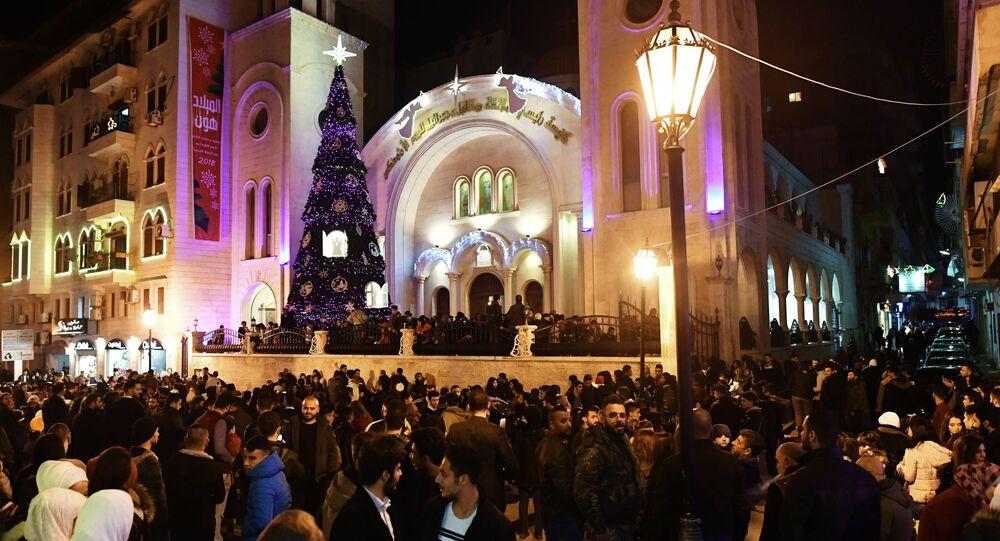 سكان مدينة اللاذقية السورية خلال الاحتفال بعيد الميلاد أمام كنيسة رئيسي الملائكة ميخائيل و جبرائيل
