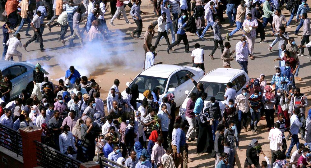 متظاهرون سودانيون يهربون من الغاز المسيل للدموع لتفريقهم أثناء مسيرتهم في الشارع خلال مظاهرات مناهضة للحكومة في الخرطوم