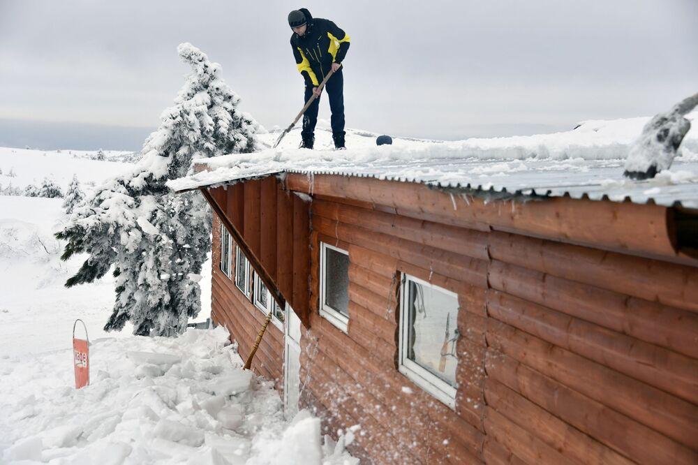 تنظيف سقف منزل من الثلوج على هضبة آي بيتري في شبه جزيرة القرم الروسية