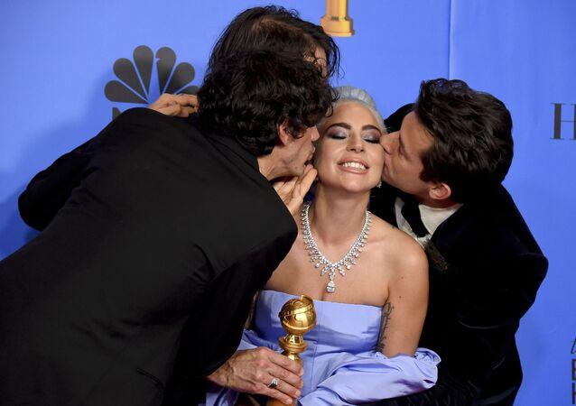 أنتوني روسوماندو، من اليسار، أندرو وايت، ومارك رونسون، على اليمين، قبله ليدي غاغا، الثاني على اليمين، وهم يحوطون بالمغنية ليدي غاغا في غرفة الصحافة حاملة جائزة أفضل أغنية أصلية، من فيلم A Star Is Born ولدت في الحفل الـ 76 لتوزيع جوائز غولدن غلوب السنوية في فندق بيفرلي هيلتون في 6 يناير/ كانون الثاني 2019 في بيفرلي هيلز، كاليفورنيا، الولايات المتحدة الأمريكية