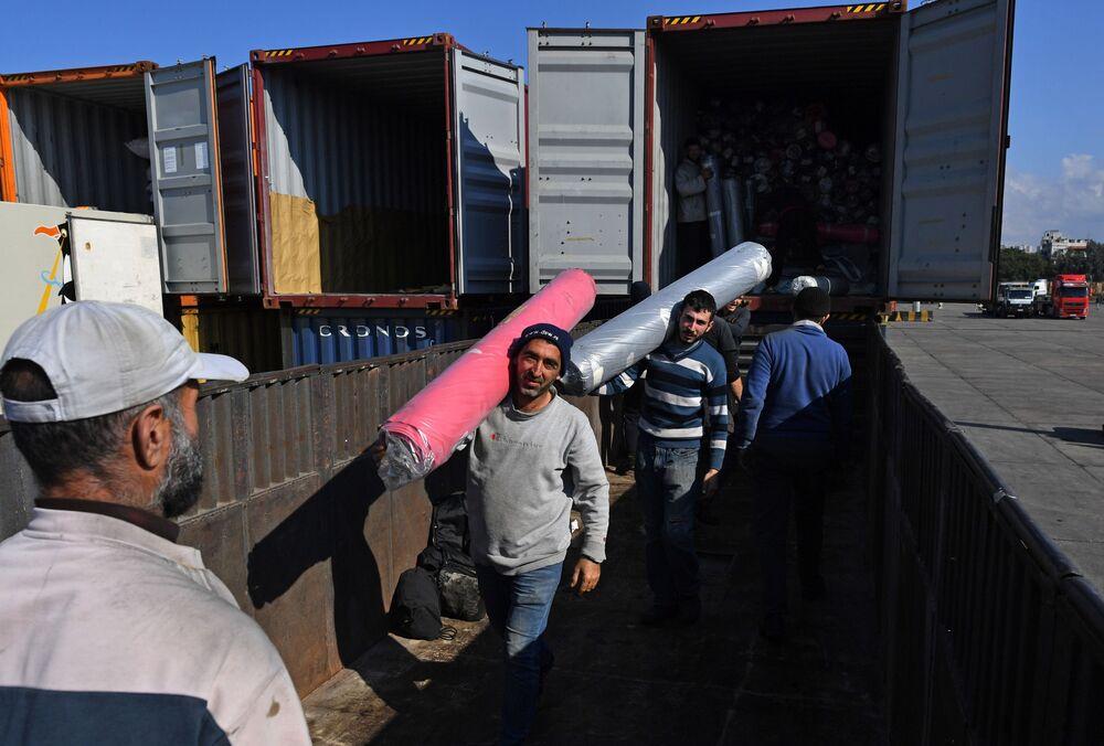 عمال يقومون بإفراغ حمولة حاويات في ميناء اللاذقية