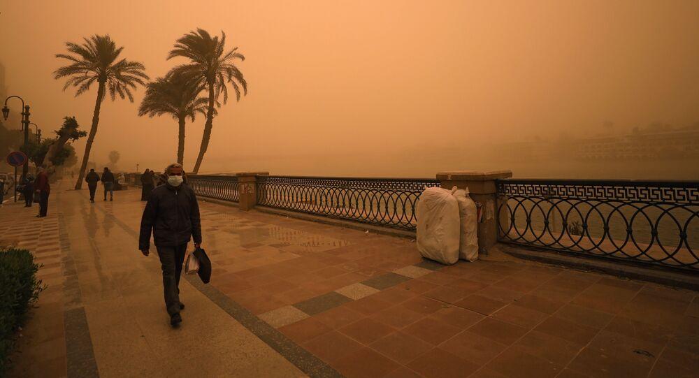 رجل يغطي وجهه خلال عاصفة رملية بالقرب من نهر النيل في القاهرة