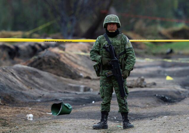 جندي في الموقع الذي انفجر فيه أنبوب الوقود بسبب لصوص في بلدية تاهويلويلبان بالمكسيك
