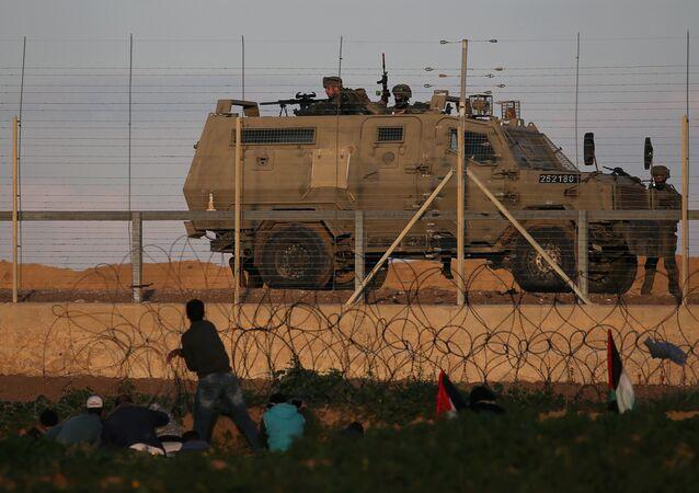 متظاهرون فلسطينيون في مواجهة القوات الإسرائيلية خلال احتجاج على السياج الحدودي بين إسرائيل وقطاع غزة