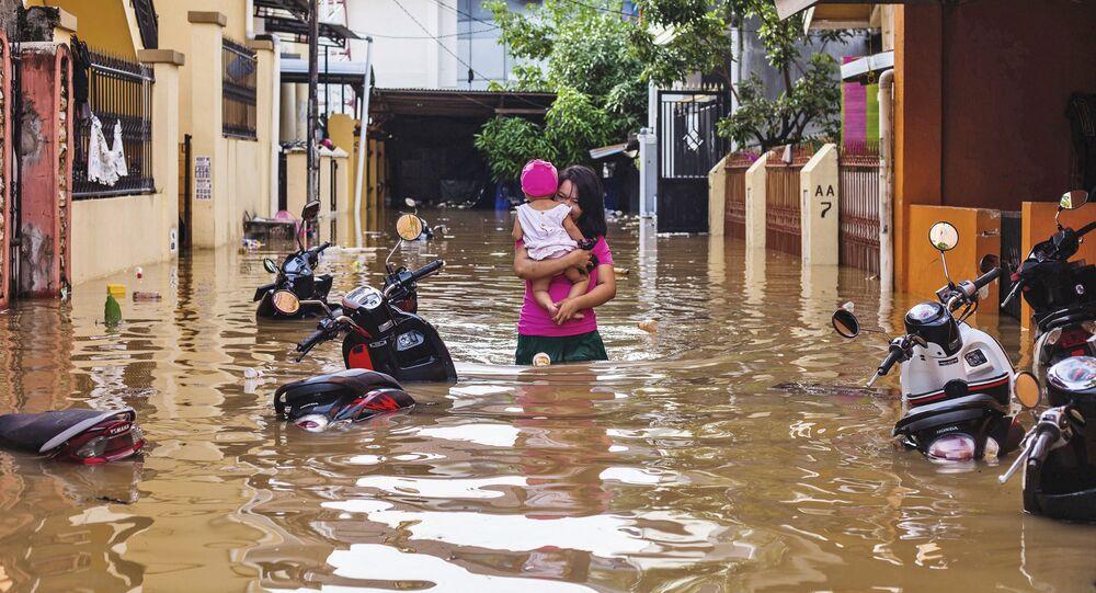 امرأة تحمل طفلها وسط مياه غمرت شوارع حي ماكاسار، إثر هطول أمطار غزيرة في إندونيسيا، 23 يناير/ كانون الثاني 2019